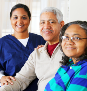 elderly couple with their caregiver smiling