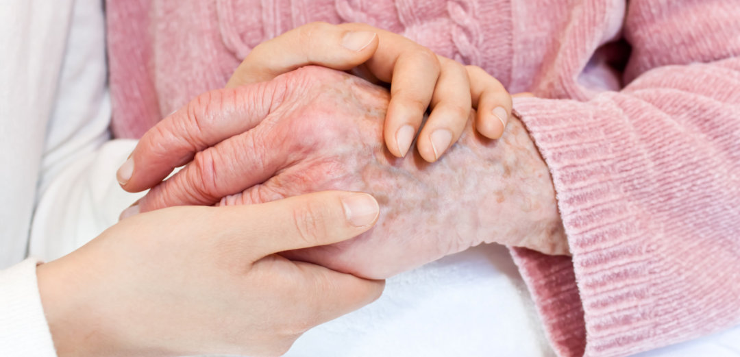 caregiver holding her patient's hand