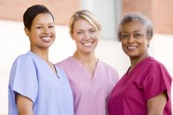 nurses standing outside a hospital smiling